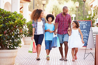 African American family shopping together at an outdoor strip mall.