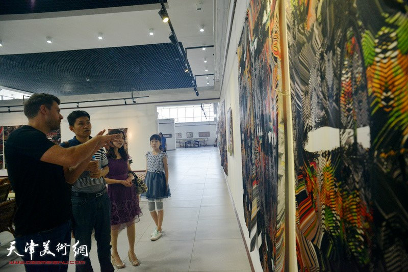 Alexes explains works at the Silk Drawings exhibition