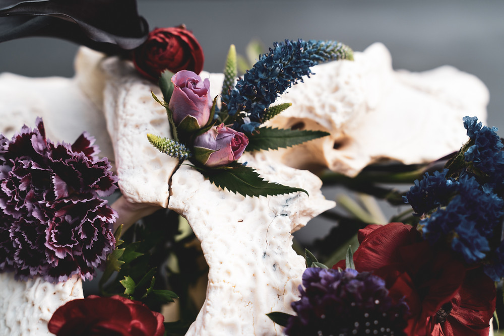 Dark flowers on bone. Offbeat flower arragement.