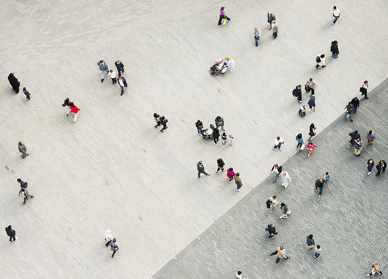 Overhead view of people walking across a brick patio. People shown represent diverse ages, genders, races, abilities.