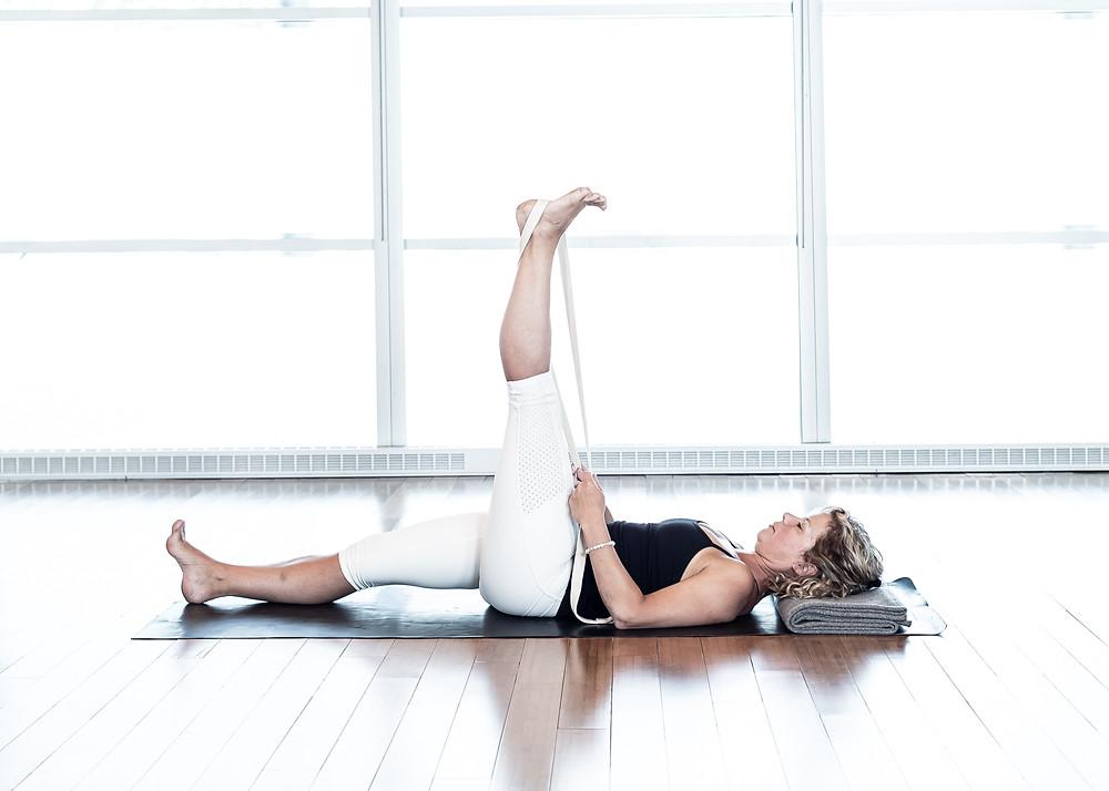 Commencer par les deux jambes pliées, les pieds au sol. Allonger complètement la jambe droite à l'aide de la courroie. Si le bas du dos le permet, allonger aussi la jambe au sol. Maintenir 10 à 20 respirations.
