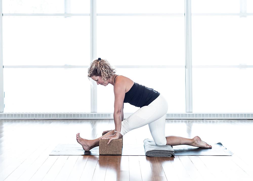 À partir de la position de la fente avec genou au sol, placer des blocs sous les mains pour garder votre colonne vertébrale allongée et tirer le bassin vers l'arrière pour tendre la jambe devant. Garder les hanches nivelées. Maintenir 10 à 20 respirations
