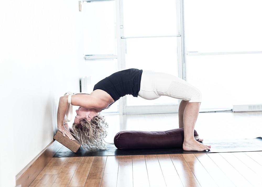 Commencer avec le bassin sur le traversin, les coudes attachés largeur de vos épaules, la tête déposé au sol avec le dessus du crâne qui touche le mur.  Soulever le bassin et ensuite, monter sur le dessus de la tête en poussant fermement dans vos mains. Ensuite essayer de faire des push up inversés en gardant les coudes près du mur. Soulever la tête du sol, répéter 3 à 5 fois.
