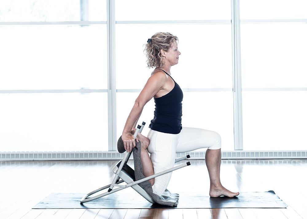 Cet étirement peut aussi se réaliser avec le genou au sol et le tibia appuye contre un mur. Ici, le genou est déposé à l'interieur de la chaise sur une couverture, allonger le coccyx vers le sol.
