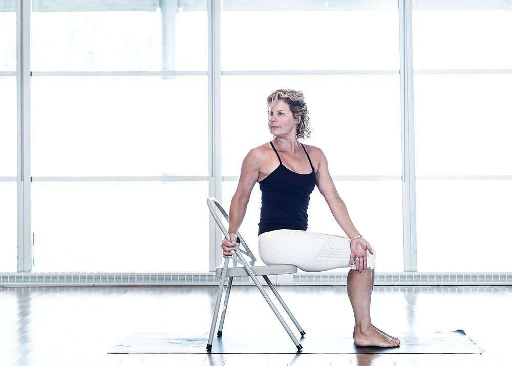 Assis sur le bout de la chaise, commencer par stabiliser votre fondation (pieds, genou, bassin). Prenez une profonde inspiration pour allonger votre colonne et commencer la torsion vers la droite à partir du bas du dos.