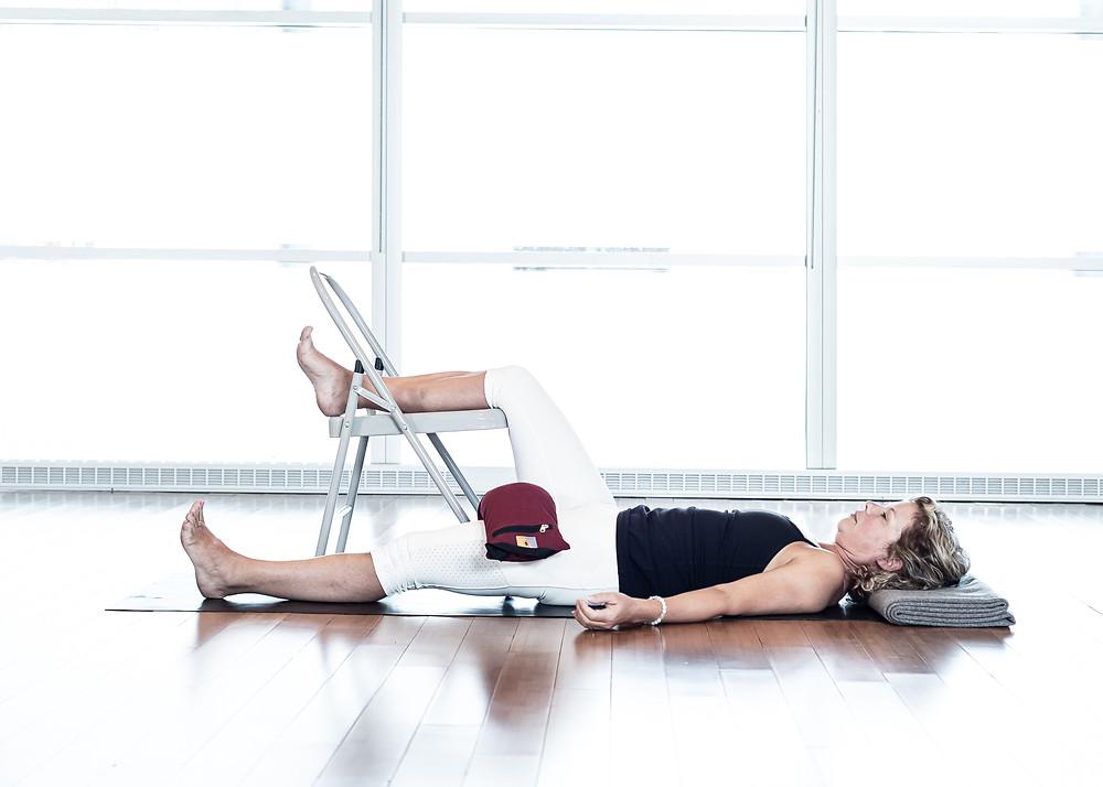 Cette posture récupératrice vous aidera à relâcher les tensions dans vos psoas. Idéalement, maintenir la posture 15 à 20 minutes par côté. Sac de sable optionnel