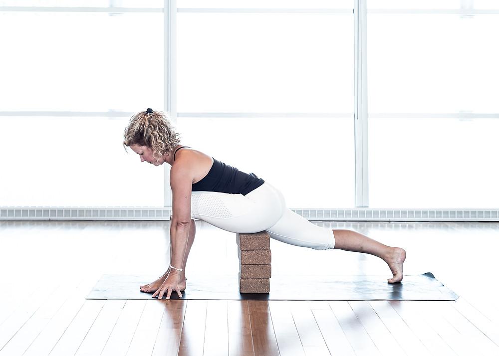 Le support des bloc nous permet de stabiliser le bassin pour ensuite allonger la jambe arrière et maintenir l'os du bassin sur le bloc. Maintenir de 10 à 20 respiration.
