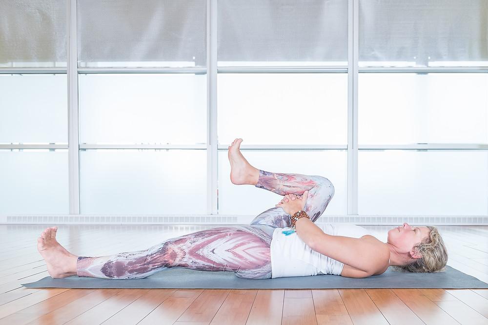 À partir d'une posture couché, maintenez une compression de l'abdomen en entrelaçant les doigts derrière la cuisse et bien tendre l'autre jambe