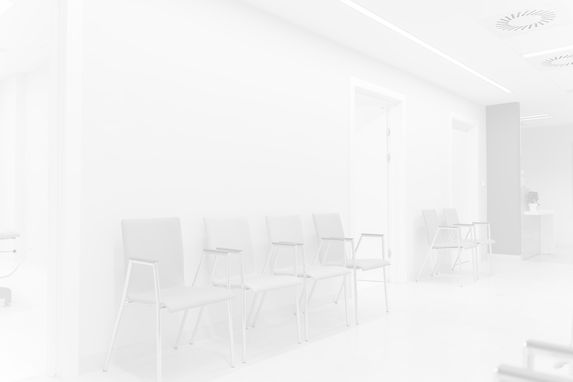 Four chairs lined up against a wall, representing the waiting area of a hospital