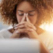 Jeune femme assise devant son ordinateur prenant une pose en fermant les yeux et en joignant les mains.