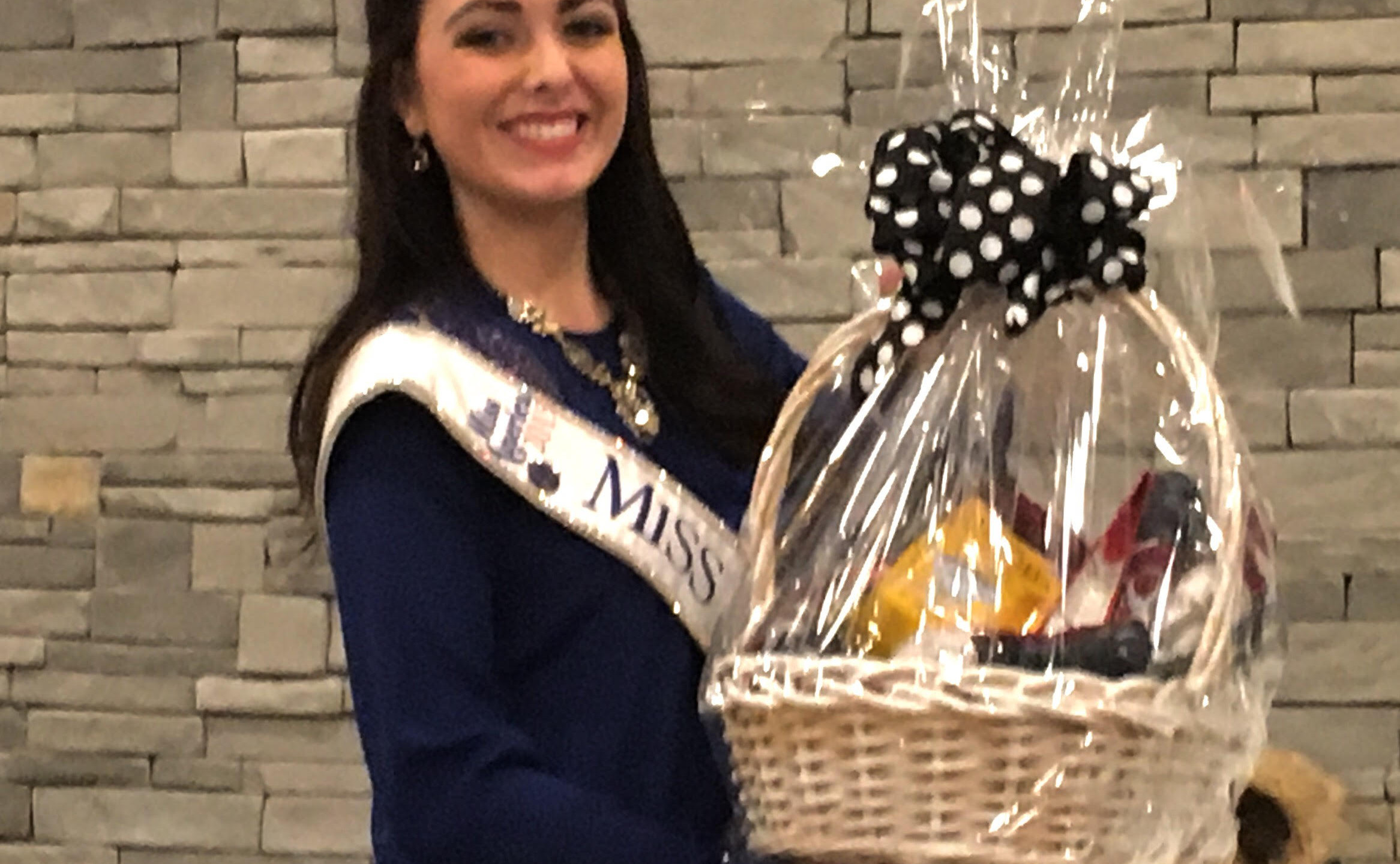 Miss Missouri McKensie Garber showing off a gift basket during the auction