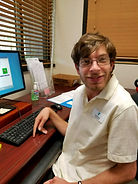 Smiling young adult male with brown hair and glasses sitting at  computer terminal