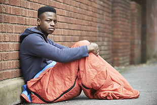 Homeless man rough sleeping outside brick wall with sleeping bag