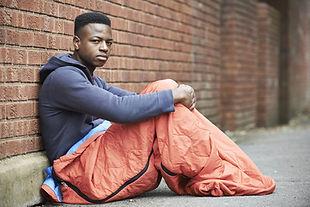 Homeless man rough sleeping outside brick wall