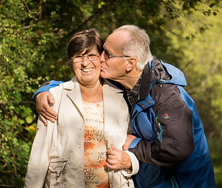 Old man kisses wife whilst walking in countryside