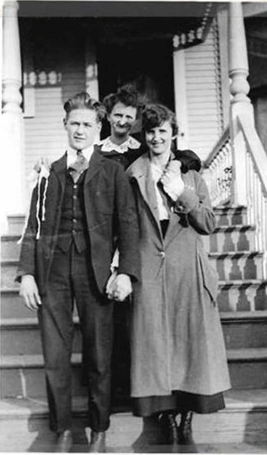 Photo of Anna Kelley holding flu mask standing behind her daughter Beryl Kelley and Larry Long on their wedding day standing in front of the Kelley residence at 518 Federal Ave E on November 11, 1918: Armistice Day and the unofficial end date of the ban on public gatherings.
