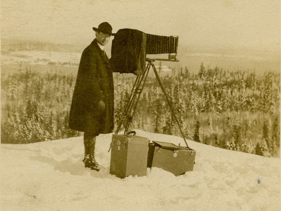 Photo of Asahel Curtis on Mount Rainier with camera and equipment. Circa 1915