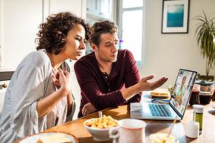 A couples talkingto a counsellor on a laptop computer