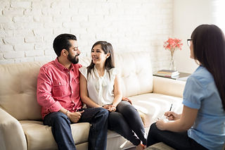 A couples sat on a couch smiling at each other whilst a counsellor looks on