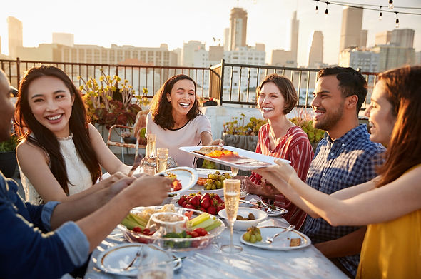Friends Gathered On Rooftop Terrace For Meal With City Skyline In Background_edited.jpg