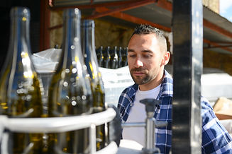 young man wine maker working filling win