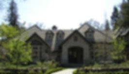 A fully landscaped front yard with a stone pathway, lawn, and shrubs