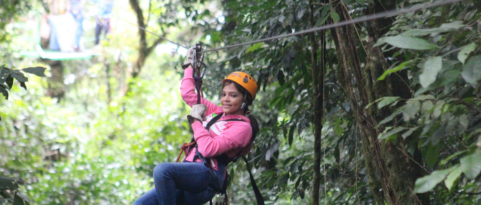 Monteverde Costa Rica zipline adventure guest in pink jacket hanging and zipping across canopy zip line