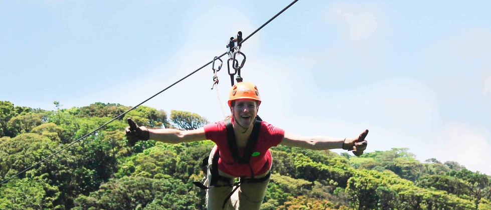 Monteverde Costa Rica zipline adventure guest zipping superman style with thumbs up