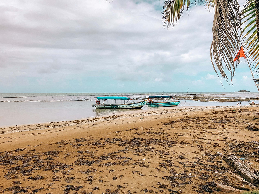 two local kuna panga speed boats anchored on deserted beach of San Blas