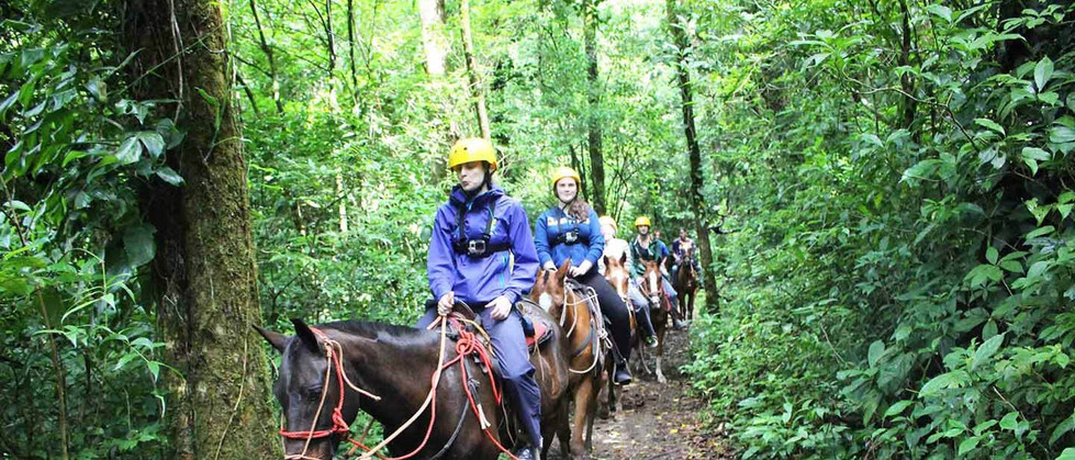 Monteverde Costa Rica guided Horseback riding tour riding on forest trail through rainforest in lush nature