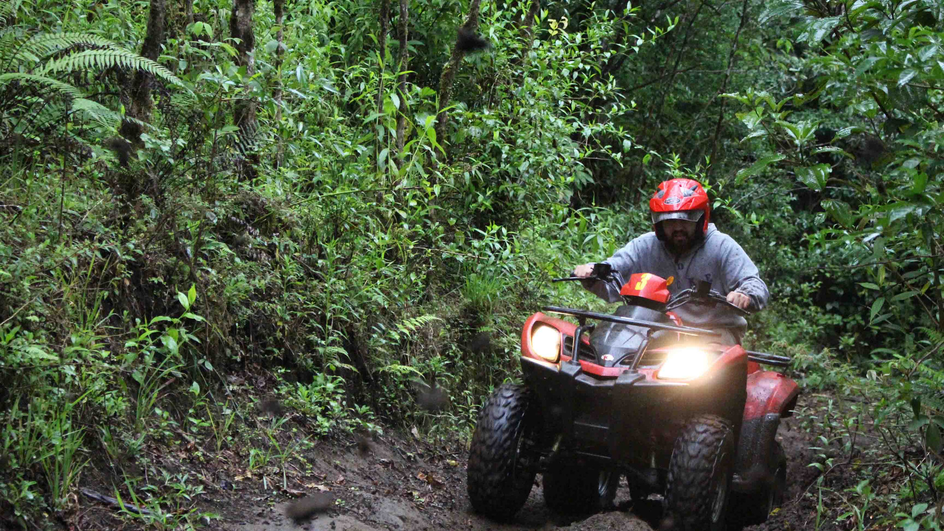 Monteverde Costa Rica ATV adventure tour group driving riding up mountain on mud trail with lights on