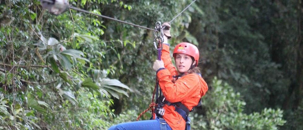 Monteverde Costa Rica zipline adventure woman guest hanging and zipping across zip line cable
