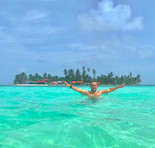 Man standing in shallow ocean on San Blas Day Tour with arms stretched out
