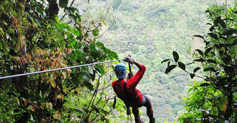 ziplining in Costa Rica man zipping on cable through rainforest