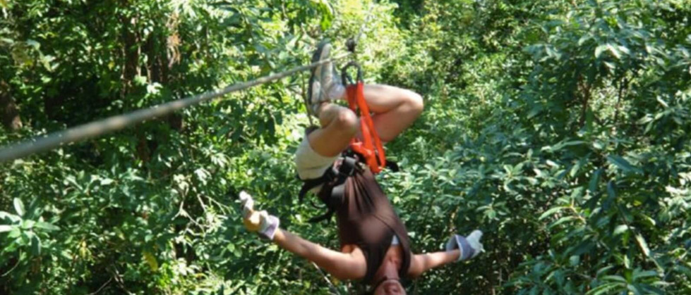 smiling man hanging upside down gliding soaring on zipline with harness and cable in Tamarindo Guanacaste Costa Rica