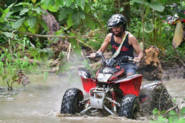 Costa Rica ATV tours guest driving through a muddy river
