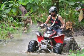 Costa Rica ATV tours guest driving through a muddy river