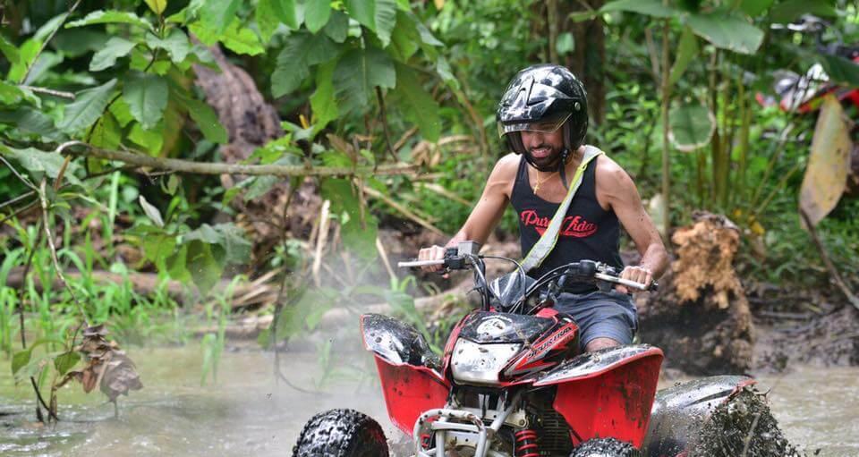 Costa Rica ATV adventure group driving through mud in jungle