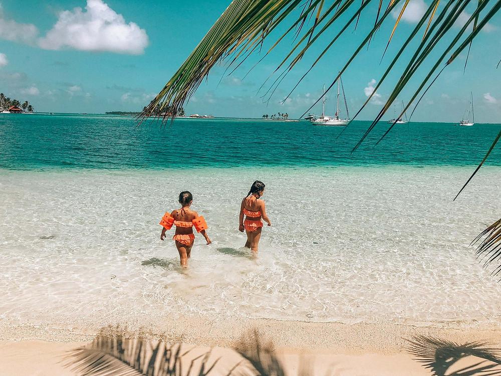 two little girls in san blas panama islands standing in clear ocean water feeding fish