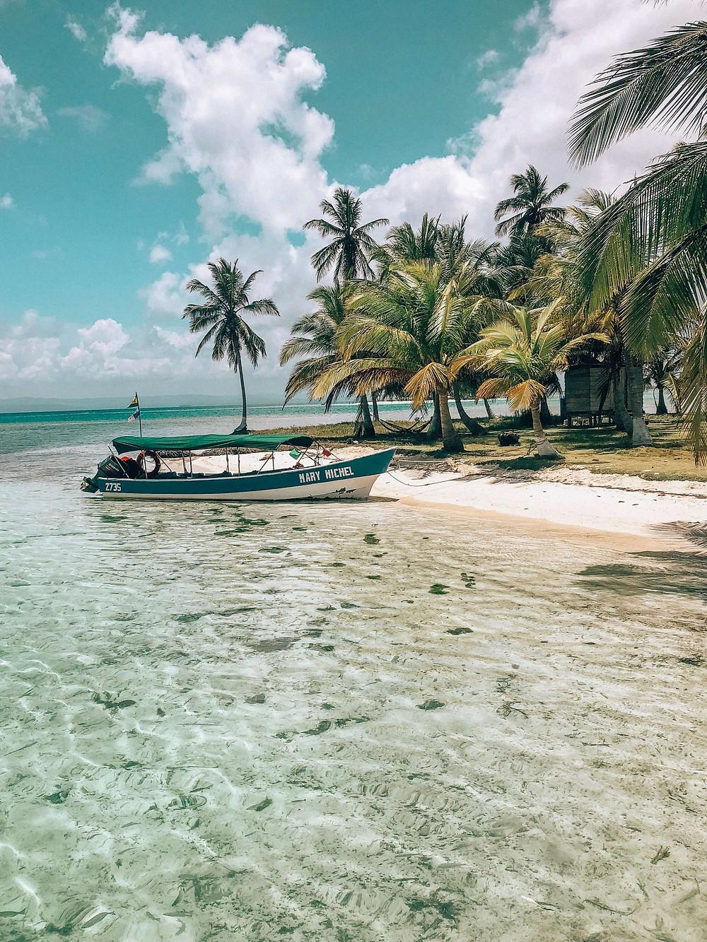 local kuna panga speed boat tied up to a palm tree in San Blas Panama