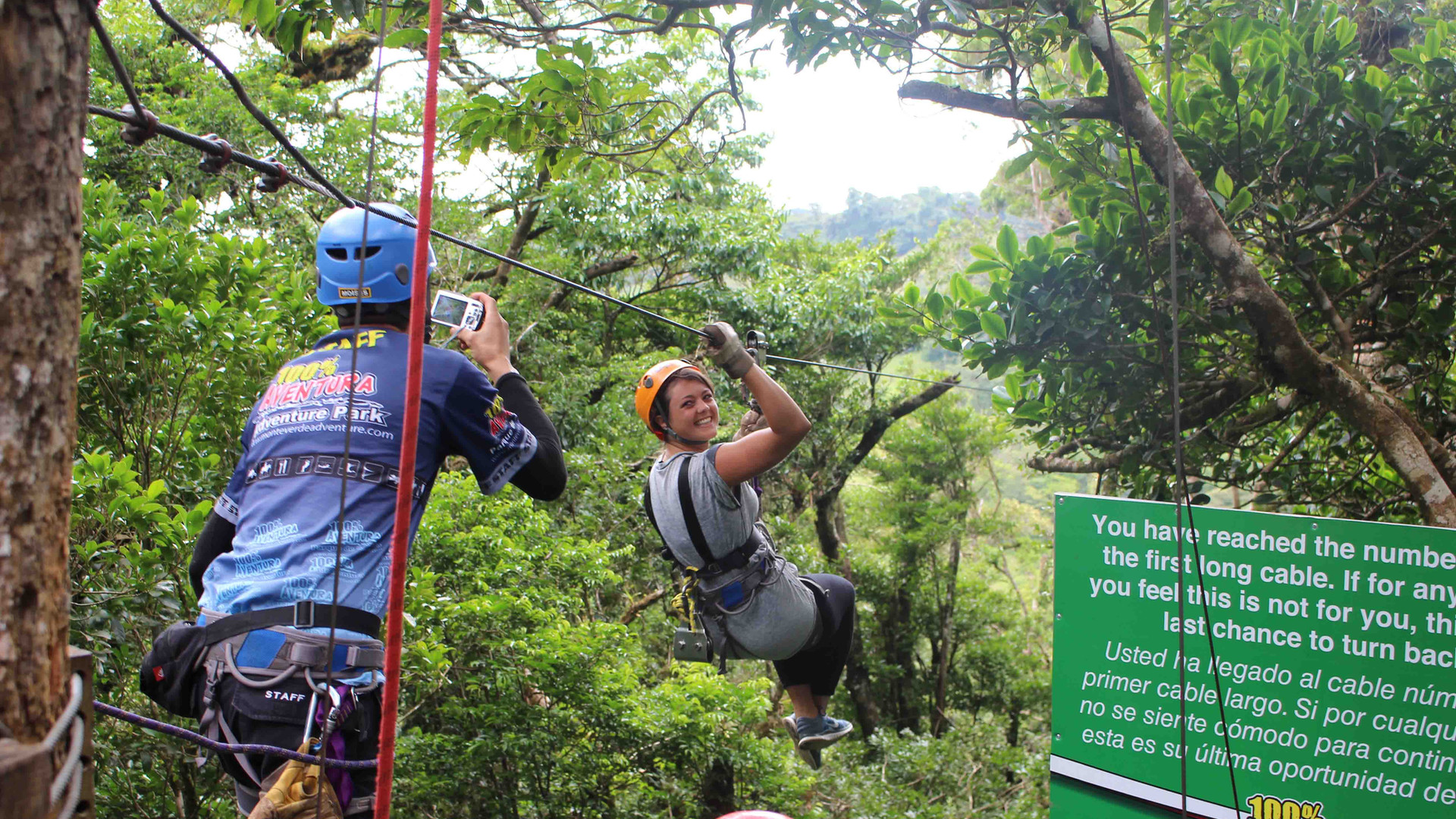 Monteverde Costa Rica zipline smiling man adventure guest hanging and zipping accross with guide taking photo
