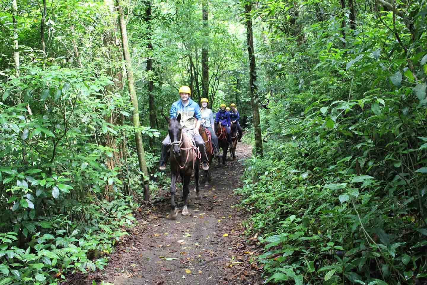 Monteverde Costa Rica guided Horseback riding tour riding on forest trail through rainforest on narrow path