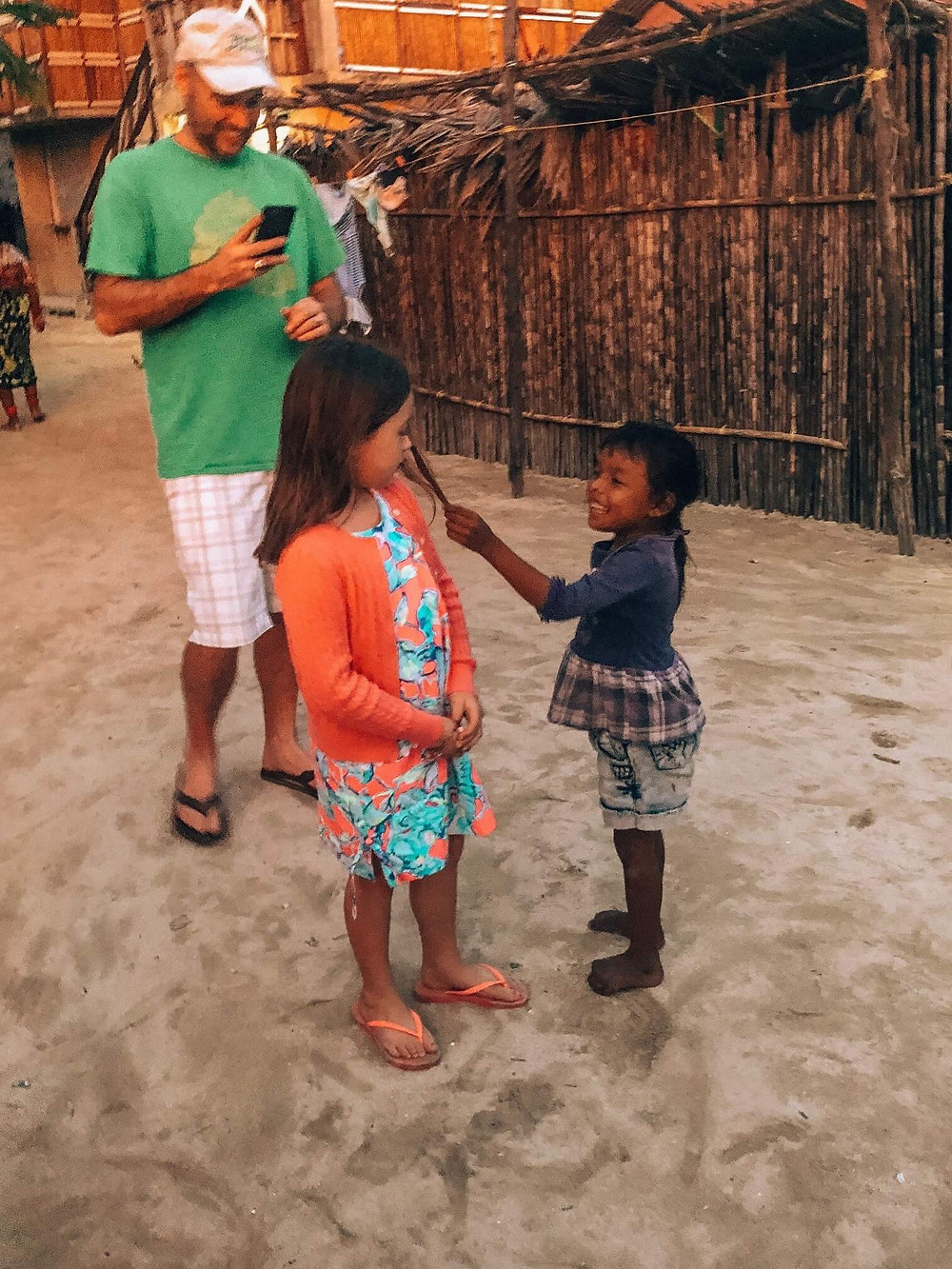 local kuna girl touching tourist girl's hair and interacting with san blas vacation guests