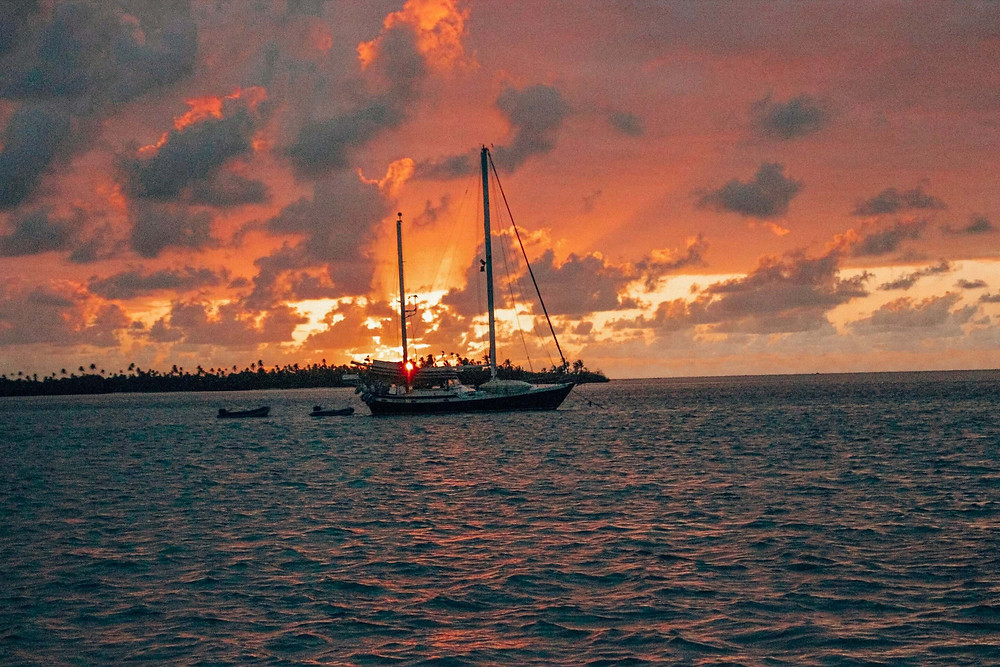 sunset in san blas panama with sailboat anchored in front of island