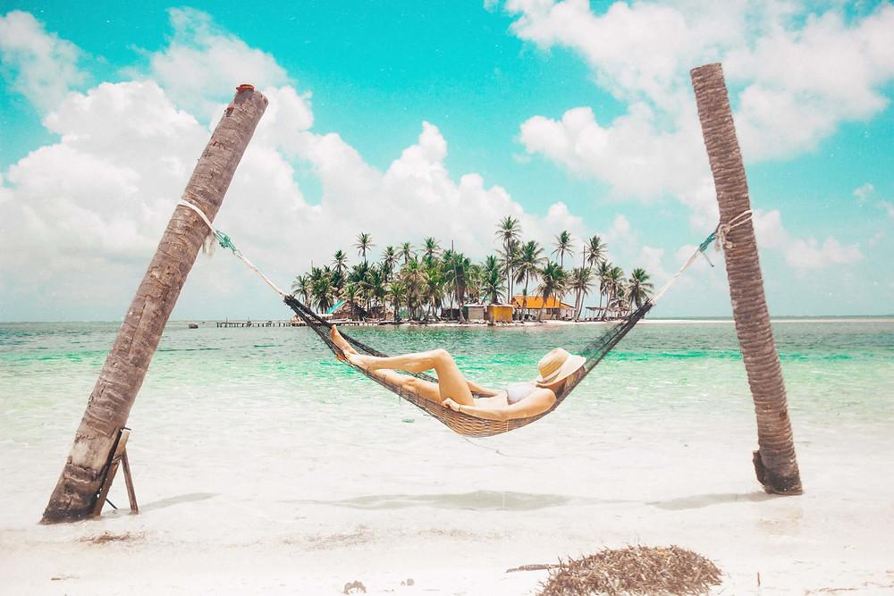 woman relaxing in hammock in san blas panama island over clear ocean