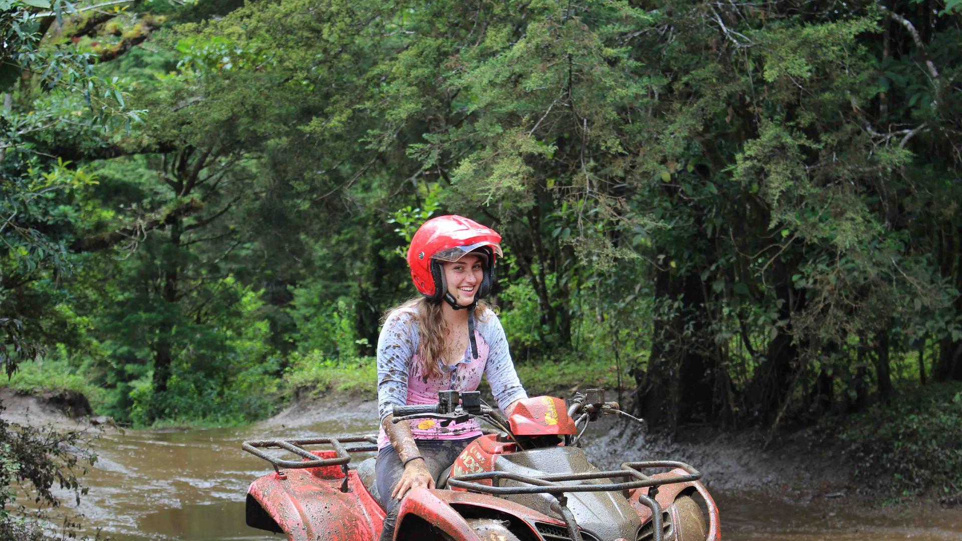 Monteverde Costa Rica ATV adventure tour woman with red helmet crossing traversing river smiling