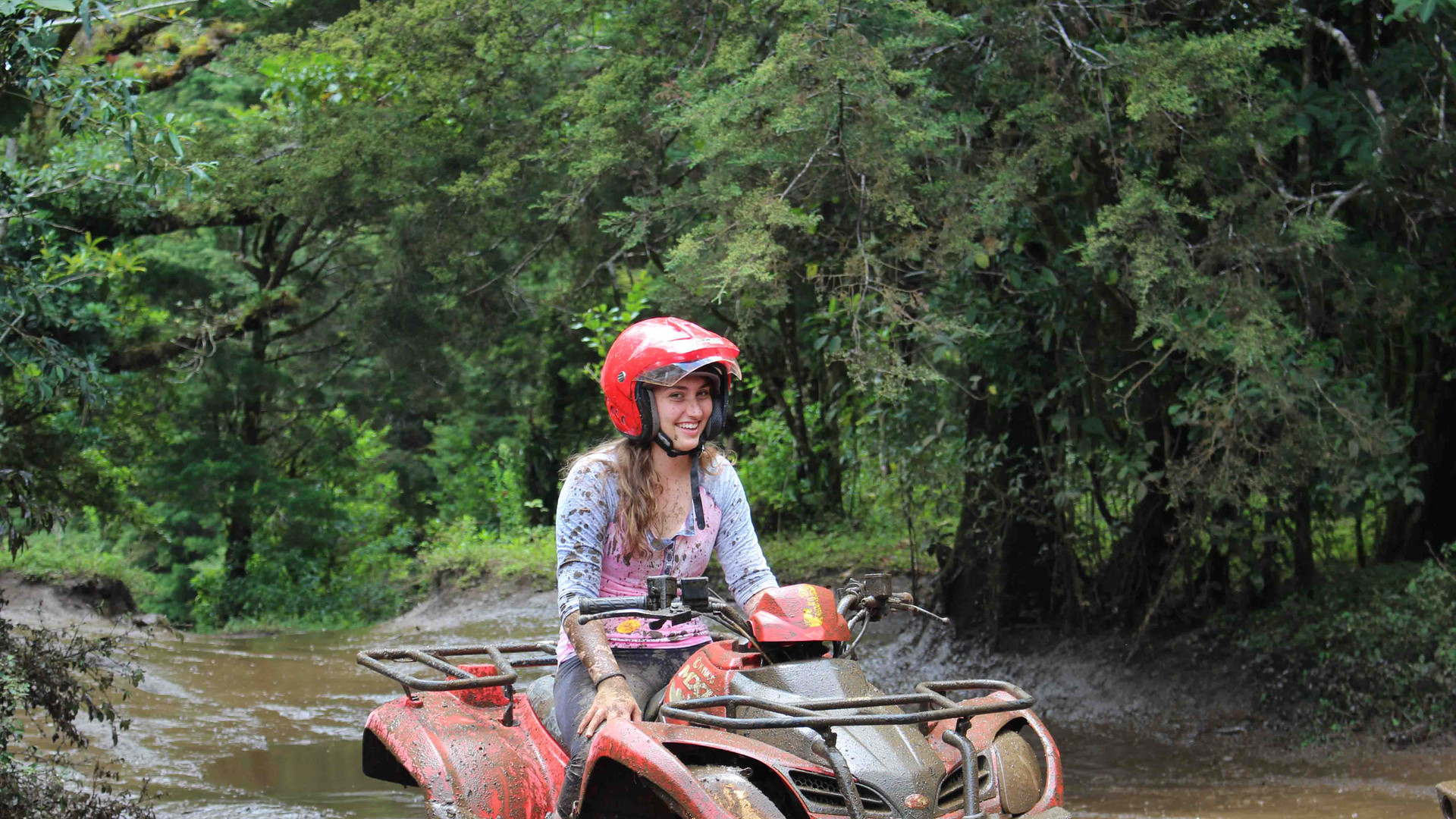 Monteverde Costa Rica ATV adventure tour woman with red helmet crossing traversing river smiling