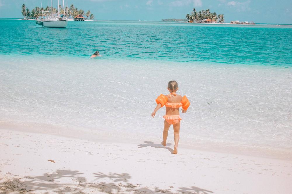 little girl with floaties in San Blas Panama islands walking into the clear ocean water
