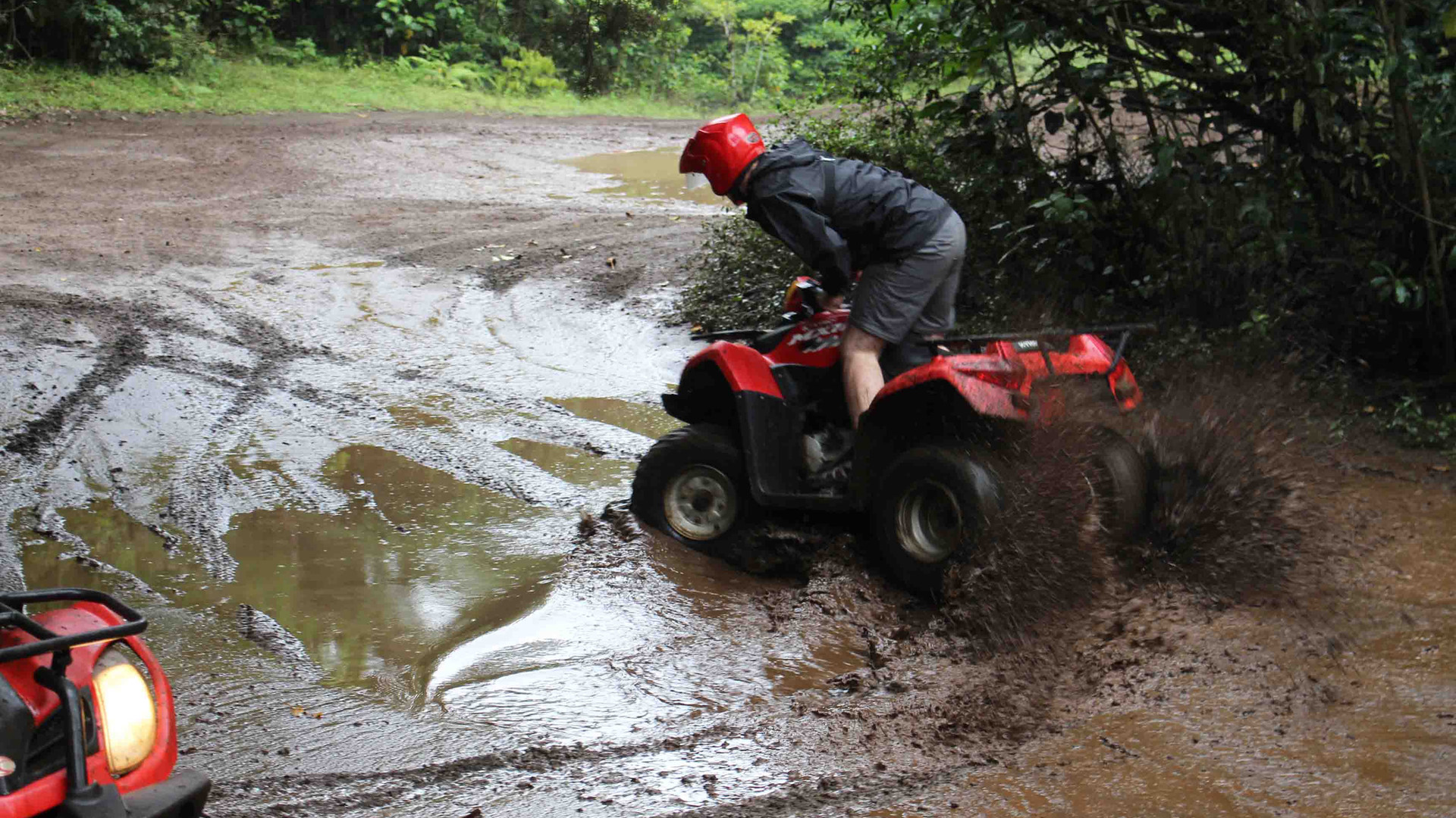 Monteverde Costa Rica ATV adventure tour group driving through mud making sliding donuts