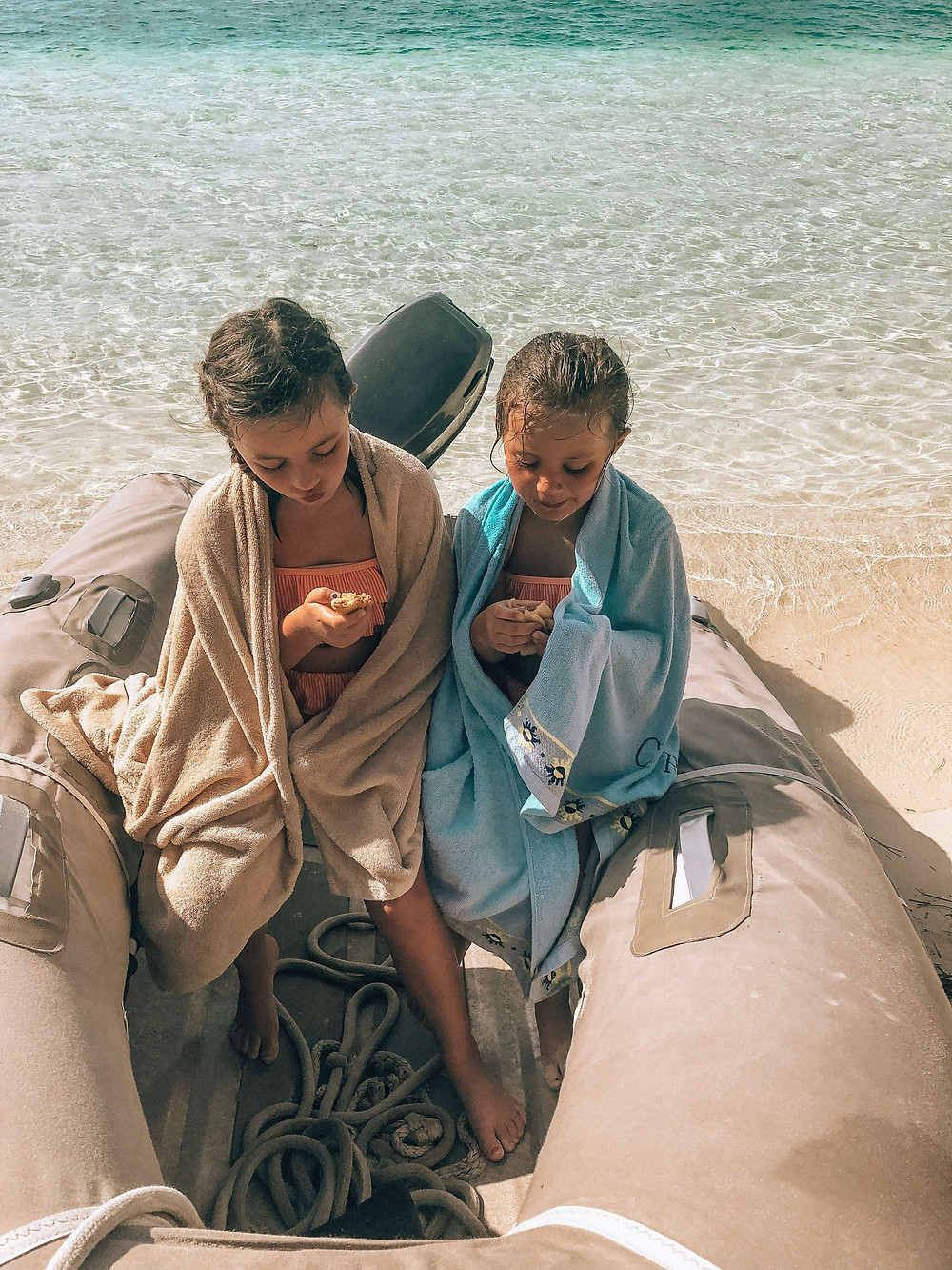 two girls sitting in a san blas sailboat charter dinghy eating fresh french crepes